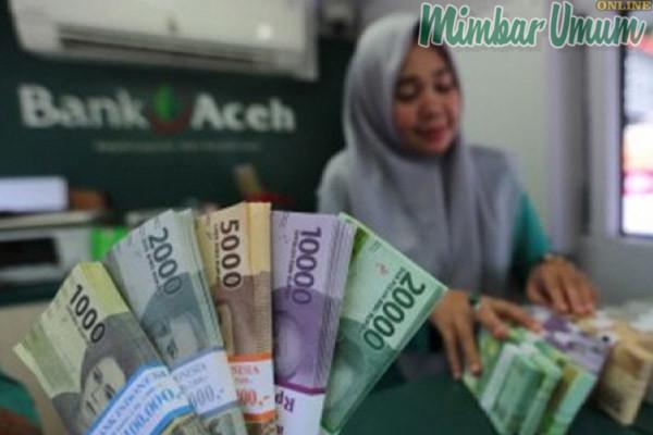 Seorang karyawati menghitung uang di salah satu kantor cabang Bank Aceh